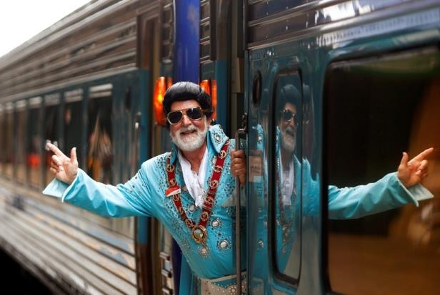 a man standing in front of a building: Elvis Presley impersonator and Mayor of the town of Parkes Ken Keith stands aboard the Elvis Express train at Sydney's Central station before it departs for the 26th annual Elvis Festival
