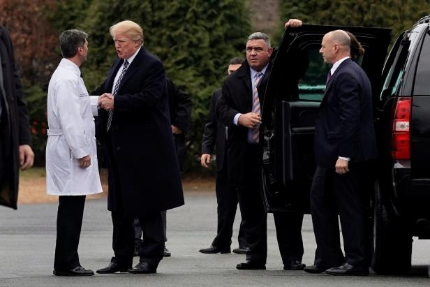 a group of people standing next to a man in a suit and tie: President Trump shaking hands with Dr. Ronny L. Jackson after having a physical exam on Friday.
