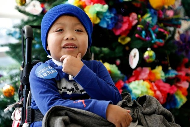 a little boy wearing a hat: Ricky Solis, 6, of Springdale, Ohio, smiles as his mother speaks Jan. 3, 2018, at Cincinnati Children's Hospital's Liberty Campus in Liberty Township, Ohio. Ricky became paraplegic after a driver crossed lanes and struck Solis and his mother, Sandra Mendez, in their car in February 2017.