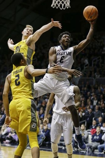 Butler guard Kamar Baldwin (3) shoots between Marquette defenders Sam Hauser (1) and Greg Elliott (5) during the first half of an NCAA college basketball game in Indianapolis, Friday, Jan. 12, 2018.