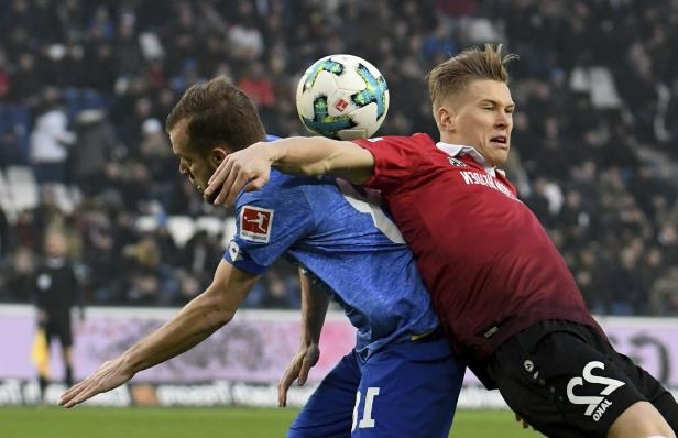 Hannover's Matthias Ostrzolek, left, and Mainz' Daniel Brosinski challenge for the ball during the German Bundesliga soccer match between Hannover 96 and FSV Mainz 05, in Hannover, Germany. Saturday, Jan. 13, 2018. (Peter Steffen/dpa via AP)