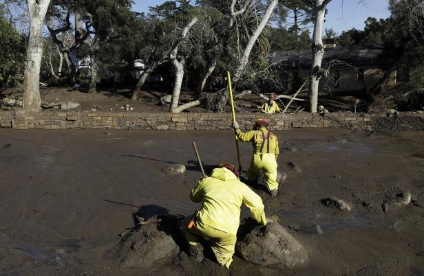 Slide 1 of 78: A Cal Fire search and rescue crew walks through mud near homes damaged by storms in Montecito, Calif., Friday, Jan. 12, 2018.  The mudslide, touched off by heavy rain, took many homeowners by surprise early Tuesday, despite warnings issued days in advance that mudslides were possible because recent wildfires had stripped hillsides of vegetation that normally holds soil in place. (AP Photo/Marcio Jose Sanchez)