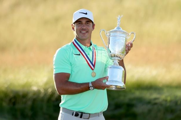 Slide 25 of 52: Brooks Koepka of the United States holds the U.S.Open trophy wearing the Jack Nicklaus medal after his four shot win in the final round of the 117th US Open Championship at Erin Hills on June 18, 2017 in Hartford, Wisconsin.