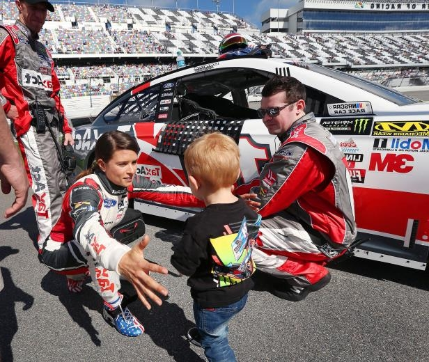 Slide 42 of 76: Danica Patrick reaches out to hug Owen Larson, 2, beside Patrick's race car on Pit Road before the start of the Clash at Daytona NASCAR race on Sunday, Feb. 19 in Daytona Beach, FL. Owen is the son of Sprint Cup driver Kyle Larson.