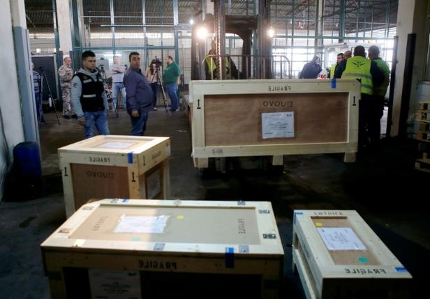 a group of people sitting at a desk: Boxes of artefacts are seen at Beirut's International Airport