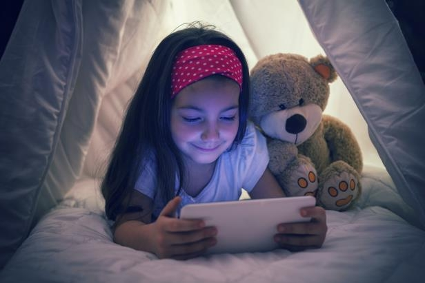 a woman holding a teddy bear: Sneakily using devices at night is disrupting young children's sleep according to a new study.