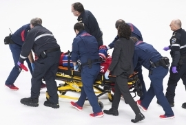 Montreal Canadiens' Phillip Danault is stretchered off the ice after he was hit in the head by a puck on a shot by Boston Bruins' Zdeno Chara during second period NHL hockey action in Montreal, Saturday, Jan. 13, 2018. (Graham Hughes/The Canadian Press via AP)