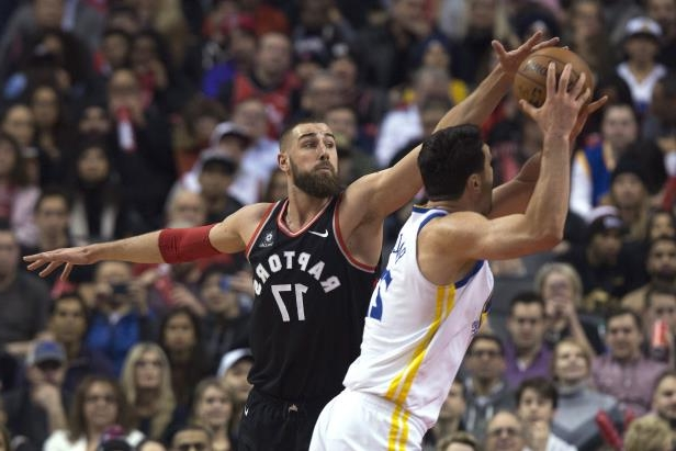 Toronto Raptors center Jonas Valanciunas (17) tries to block a shot by Golden State Warriors center Zaza Pachulia (27) during the first half of an NBA basketball game Saturday, Jan. 13, 2018, in Toronto. (Cole Burston/The Canadian Press via AP)