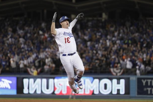 a man standing in front of a crowd of people watching a baseball game: The Los Angeles Dodgers' Joc Pederson rounds the bases following his solo home run in the seventh inning against the Houston Astros during Game 6 of the World Series on Tuesday, Oct. 31, 2017, at Dodger Stadium in Los Angeles.