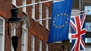 a flag hanging on a brick building: Brexit An Economic Disaster?
