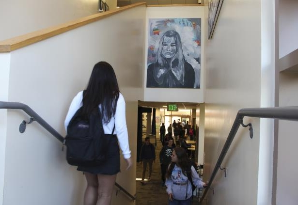 In this Tuesday, Jan. 30, 2018 photo provided by Sophia Muys, students pass under one of James Franco's paintings displayed above a stairwell in the Media Arts Center at Palo Alto High School in Palo Alto, Calif. Actor and director Franco is a 1996 graduate of the school. Franco's former high school has taken down a mural he painted and plans to remove other art donated by the celebrity alumnus who is facing allegations of sexual misconduct in Hollywood. A statement from the school district Thursday, Feb. 1, 2018, said removing the artwork was