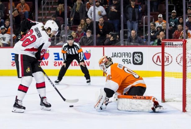 a hockey game in the snow: Ottawa Senators forward Mike Hoffman shoots the puck past Philadelphia Flyers goalie Michal Neuvirth for the game-winning goal during a shootout in Philadelphia on Saturday. The Senators won 4-3.