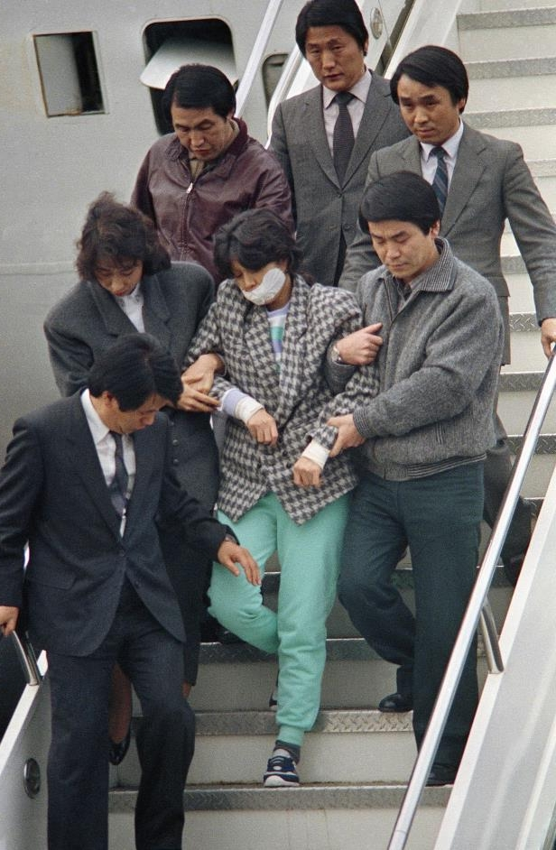 a group of people standing around each other: Kim Hyon-hui, her mouth taped, is escorted from a plane after arriving in Seoul following her arrest.
