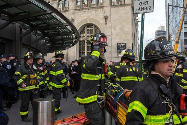a group of people wearing costumes and standing in front of a building: A Long Island Rail Road commuter train crashed inside the Atlantic Terminal in Brooklyn last year, injuring more than 100 people.
