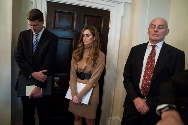 John F. Kelly et al. standing next to a man in a suit and tie: Chief of Staff John F. Kelly, left, Hope Hicks and Rob Porter pray during a Cabinet meeting at the White House in December.
