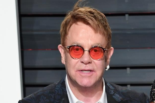 Elton John wearing glasses and smiling at the camera: PA/PA Wire