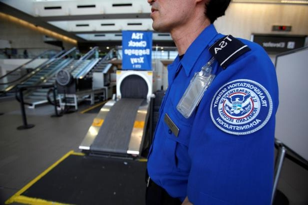 A Transportation Security Administration (TSA) officer waits by an X-ray machine at Los Angeles International Airport in Los Angeles, California March 4, 2013.