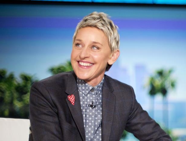 ELLEN DEGENERES wearing a suit and tie smiling at the camera: Ellen DeGeneres appears during a taping of