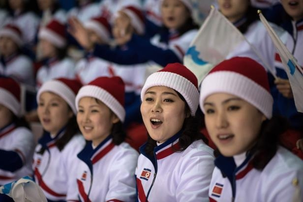a group of people posing for the camera: North Korean cheerleaders attend the women's preliminary round ice hockey match between Sweden and Unified Korea during the Pyeongchang 2018 Winter Olympic Games at the Kwandong Hockey Centre in Gangneung on February 12, 2018.