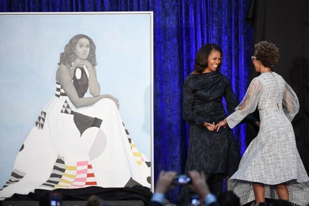 a group of people standing in a room: Michelle Obama and Amy Sherald, left, at the unveiling of Sherald's portrait of the former first lady at the National Portrait Gallery on Monday. In the portrait, Obama wears a gown by Michelle Smith's fashion line, Milly. (Matt McClain/The Washington Post)