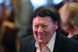 Marty Allen wearing a suit and tie smiling at the camera