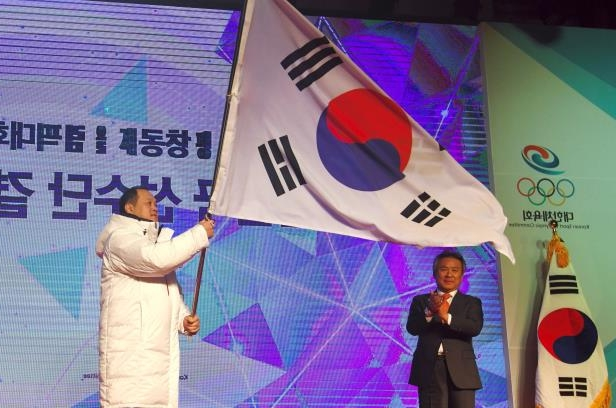 Slide 102 of 121: Kim Ji-Yong (R), head of the South Korean Olympic squad, waves the national flag during a ceremony to launch the South Korean delegation to the Pyeongchang Winter Olympic Games, in Seoul on January 24, 2018.  / AFP PHOTO / JUNG Yeon-Je        (Photo credit should read JUNG YEON-JE/AFP/Getty Images)