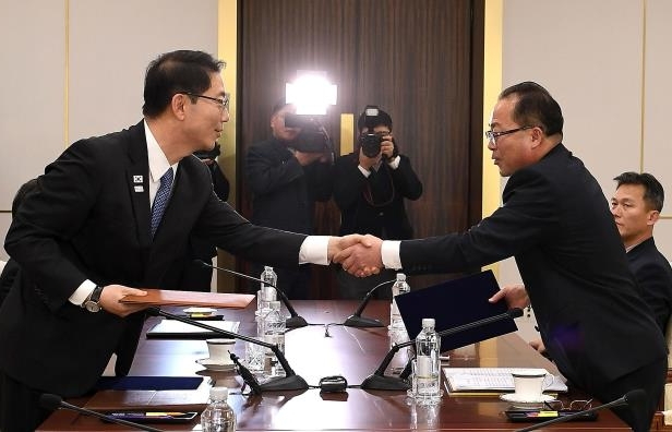Slide 117 of 121: In this handout image provided by the South Korean Unification Ministry, South Korean Vice Unification Minister Chun Hae-Sung, (R) shakes hands with the head of North Korean delegation Jon Jong-Su (L) after their meeting on January 17, 2018 in Panmunjom, South Korea. South and North Korea agreed to field a joint women's ice hockey team for the PyeongChang Winter Olympics and march together under a