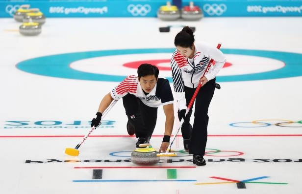 Slide 50 of 121: GANGNEUNG, SOUTH KOREA - FEBRUARY 11:  Jang Hye-ji and Lee Ki-jeong of South Korea compete during the Curling Mixed Doubles on day two of the PyeongChang 2018 Winter Olympic Games at Gangneung Curling Centre on February 11, 2018 in Gangneung, South Korea.  (Photo by Dean Mouhtaropoulos/Getty Images)