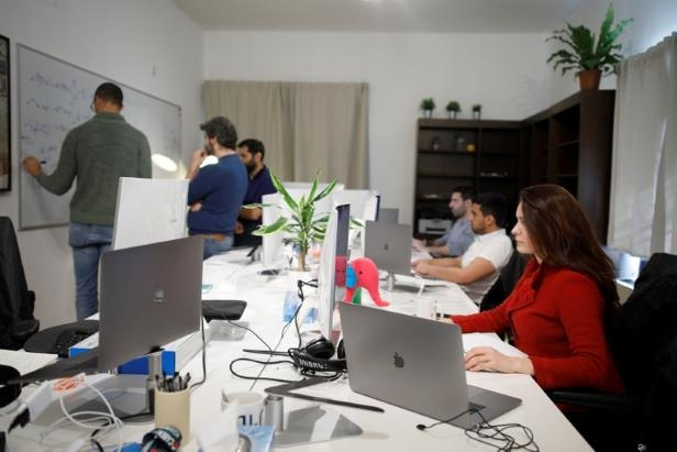 a group of people sitting at a desk: Employees of the D-ID startup company work at the company's office in Tel Aviv.