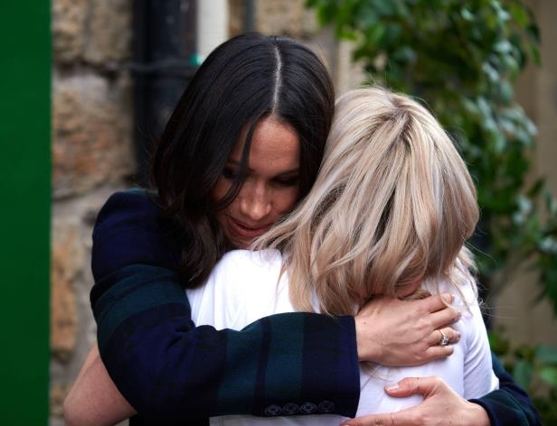 a person talking on a cell phone: Meghan Markle hugs Alice Thompson during a visit to the Social Bite social enterprise cafe in Edinburgh, Scotland, on Feb. 13, 2018.