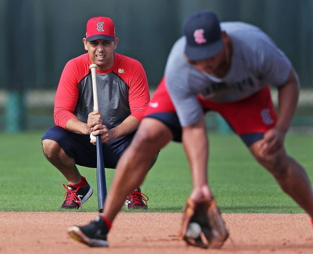 Boston Red Sox manager Alex Cora, right, watches third baseman Rafael Devers take ground balls during a workout at the Player Development Complex at Jet Blue Park in Fort Myers, FL on Feb. 13, 2018.