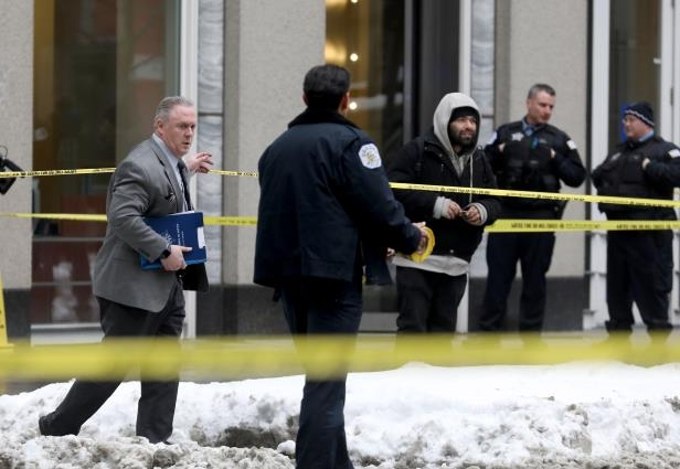 Police guard the crime scene after an off-duty Chicago police officer was shot at the James R. Thompson Center on Tuesday, Feb. 13, 2018 in Chicago, Ill.