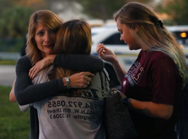 Kristi Gilroy (R), hugs a young woman at a police check point near the Marjory Stoneman Douglas High School where 17 people were killed by a gunman yesterday, on February 15, 2018 in Parkland, Florida.