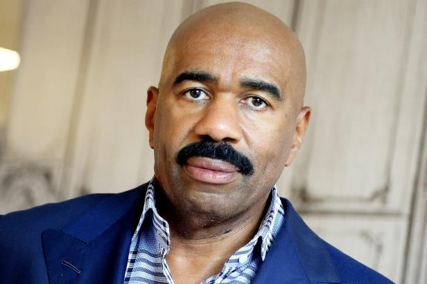 STEVE HARVEY wearing a blue shirt and smiling at the camera