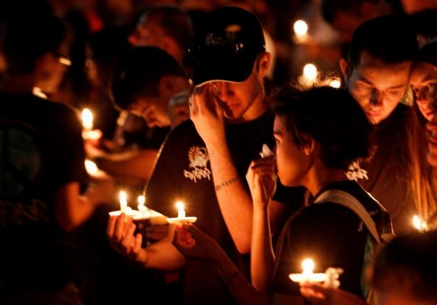 Slide 25 of 46: Thousands of mourners hold candles a candlelight vigil for victims of the Marjory Stoneman Douglas High School shooting in Parkland, Florida on February 15, 2018.  A former student, Nikolas Cruz, opened fire at the Florida high school leaving 17 people dead and 15 injured. / AFP PHOTO / RHONA WISE        (Photo credit should read RHONA WISE/AFP/Getty Images)