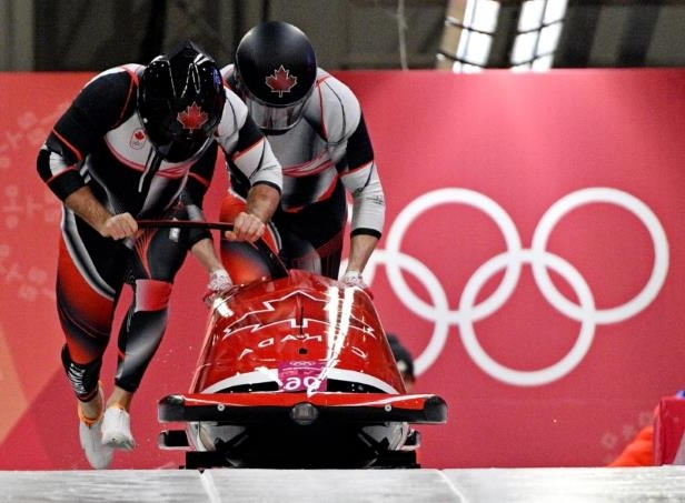 a man riding a red motorcycle: Olympics: Bobsleigh