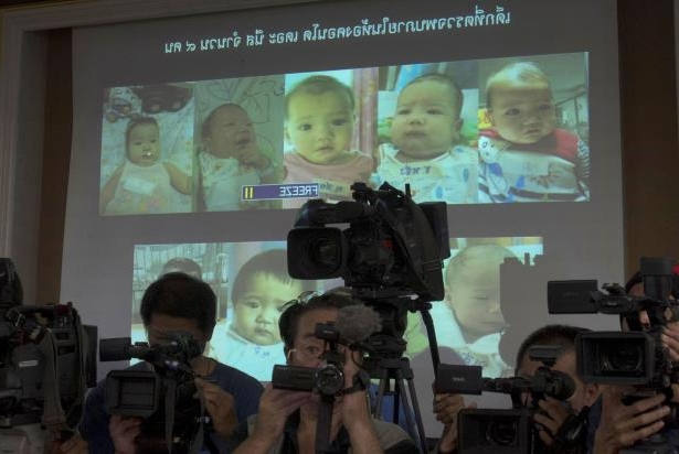 FILE - In this Aug. 12, 2014, file photo, the media attend a press briefing where Thai police display projected pictures of surrogate babies born to a Japanese man who is at the center of a surrogacy scandal during a press conference at the police headquarters in Chonburi, Thailand. The Japanese father of the surrogate babies Mitsutoki Shigeta is the son of the founder of Japanese telecom and insurance company Hikari Tsushin and earns millions of dollars a year in dividends. (AP Photo/Sakchai Lalit, File): At a press briefing in 2014 in Chonburi, Thailand, police showed pictures of surrogate babies born to Mitsutoki Shigeta.
