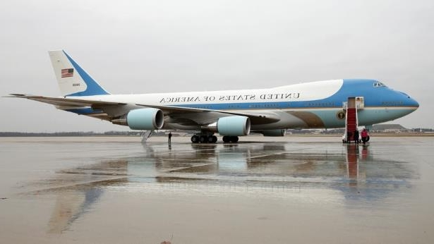 9e9935fbc a blue and white airplane on a runway at an airport: President Trump has  struck