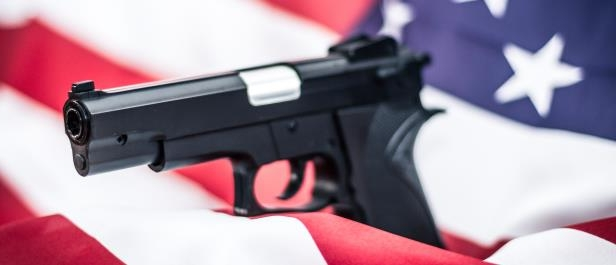 A gun wrapped in an American flag. (Shutterstock)