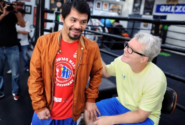 Manny Pacquiao standing in front of a crowd: Boxing trainer Freddie Roach and Manny Pacquiao share a laugh after a workout at the Wild Card Boxing Gym on March 31, 2016 in Los Angeles.