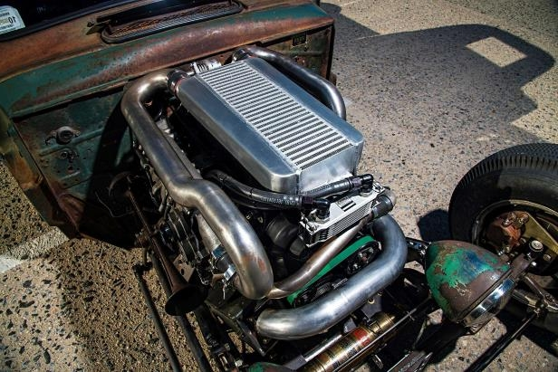 a motorcycle is parked in the dirt: 1949 Ford F3 Pickup Rat Rod