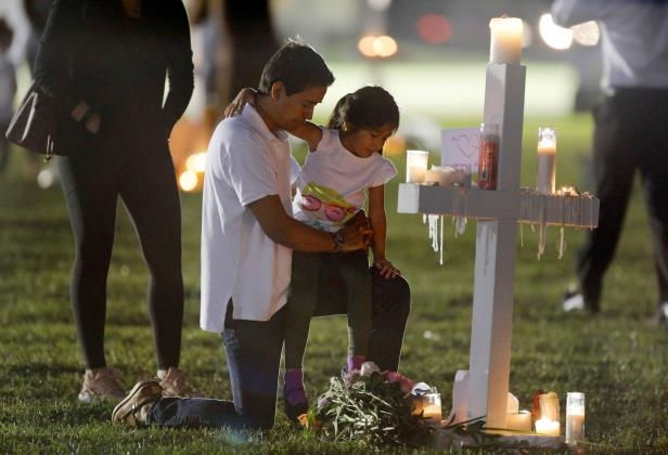 A father and daughter visit one of 17 crosses at a memorial for the victims of the shooting at Marjory Stoneman Douglas High School in Parkland, Florida, U.S. February 16, 2018