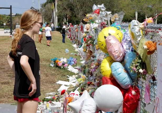 Former Marjory Stoneman Douglas High School student Madisyn Coles views memorials on a fence surrounding the school in Parkland, Florida, U.S., February 23, 2018