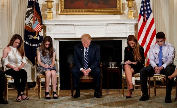 From left, Marjory Stoneman Douglas High School student Jonathan Blank, Julia Cordover, the student body president at Marjory Stoneman Douglas High School, President Donald Trump, Marjory Stoneman Douglas High School student students Carson Abt, and Ariana Klein, bow their heads during the opening prayer before a listening session with high school students, teachers, and others in the State Dining Room of the White House in Washington, Wednesday, Feb. 21, 2018.
