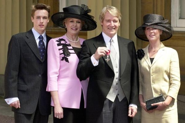 a couple of people standing next to a person in a suit and tie: William Roache with his daughter Verity, wife Sara and son William after he received his MBE in 2001 (Image: PA)