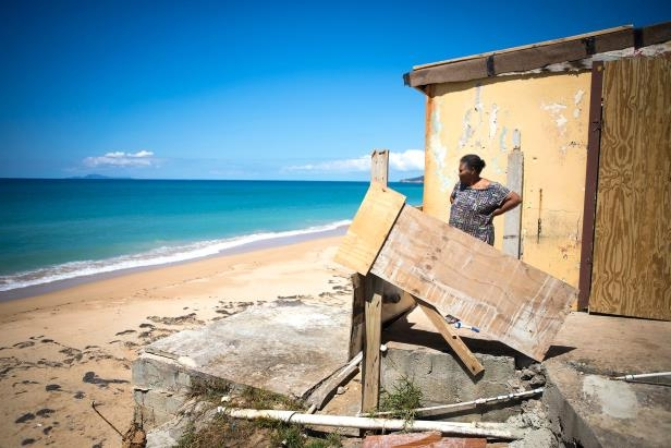 a person sitting at a beach: Irma Torres, 75, looks out over the ocean on Feb. 28, 2018 in Yabucoa, Puerto Rico. Maria tore off part of her roof and pushed the sea right up to her kitchen window.
