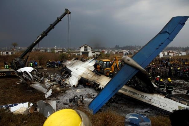 a crane in the background: Rescue workers work at the wreckage of a US-Bangla airplane after it crashed at the Tribhuvan International Airport in Kathmandu