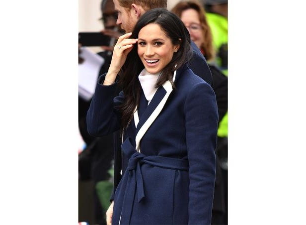 Meghan Markle baptism: Meghan Markle wears a white top and navy blue coat and touches her hair: (Photo: Rex Shutterstock)