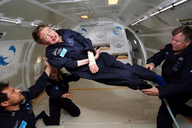 a group of people standing around a plane: Dr. Hawking pushed the limits in his professional and personal life. In 2007, when he was 65, he took part in a zero-gravity flight aboard a specially equipped Boeing 727.