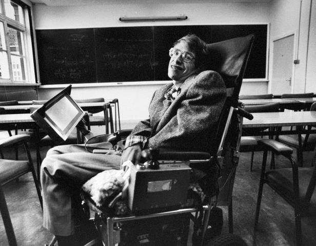 a person sitting in a chair in front of a laptop: Stephen Hawking became a leader in exploring gravity and the properties of black holes. His work led to a turning point in the history of modern physics.